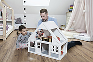 Father and toddler daughter playing with doll house in her nursery - SBOF00594