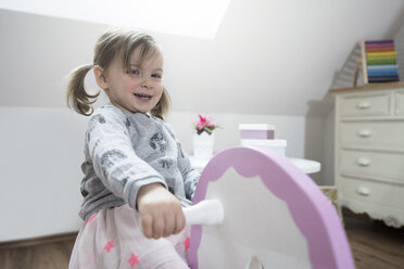 Happy toddler girl rocking on rocking horse in nursery - SBOF00600