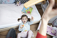 Toddler girl pointing at mother's hand holding a toy plane - SBOF00606