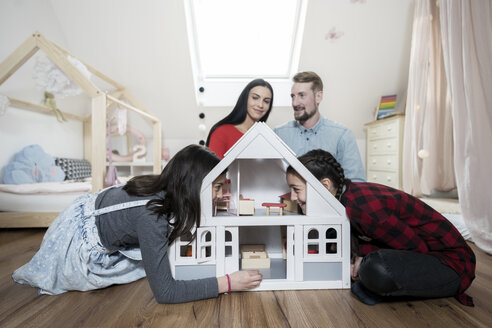 Parents and twin daughters playing with doll house in nursery - SBOF00612