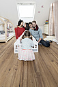 Happy family with three daughters playing with doll house in nursery - SBOF00615