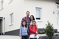 Portrait of parents and twin daughters in front of their family home - SBOF00621