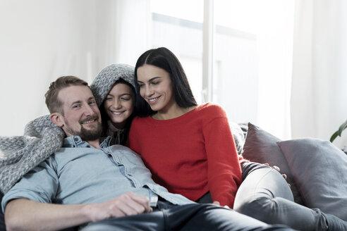 Parents and daughter cuddling under blanket on sofa in living room - SBOF00624