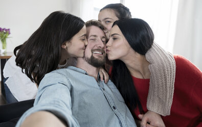 Father taking a selfie while mother and twin daughters kissing him - SBOF00627