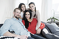 Family portrait of parents and twin daughters on sofa in living room - SBOF00630
