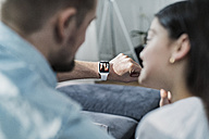 Daughter and father looking at smartwatch with mother waving at them - SBOF00639