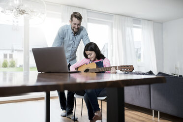 Father smiling at daugher playing guitar in front of laptop - SBOF00642