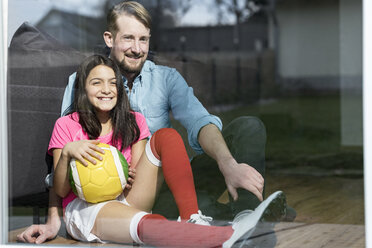 Girl in soccer outfit sitting next to father on floor in living room looking out window - SBOF00651