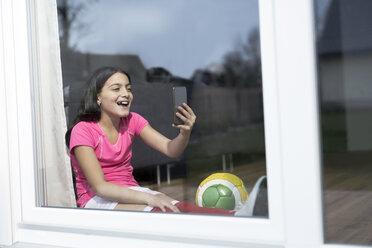 Happy girl in soccer outfit sitting on floor in living room taking a selfie - SBOF00657