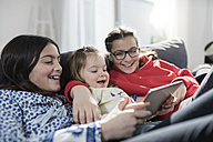 Three sisters smiling and holding tablet on sofa in living room - SBOF00660
