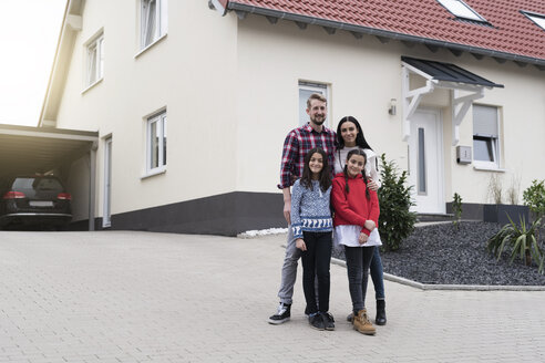 Portrait of parents and twin daughters in front of their family home - SBOF00666