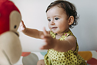 Baby girl playing with a cuddly toy - GEMF01796