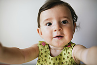 Portrait of baby girl stretching out her arms on white background - GEMF01799