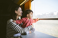 Mother and baby girl traveling by train looking out of window - GEMF01805