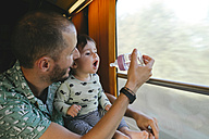 Father giving water to his baby girl in a baby bottle while traveling by train - GEMF01811