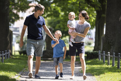 Happy family with two children walking in park - MIDF00851