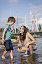 Germany, Friedrichshafen, Lake Constance, happy mother and son with toy boat at lakeshore - MIDF00863