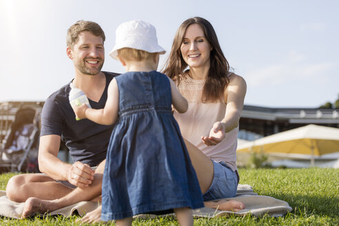 Happy family with little daughter on a meadow - MIDF00866