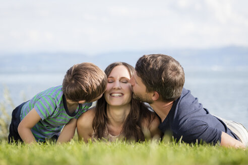 Germany, Friedrichshafen, Lake Constance, father and son kissing happy mother - MIDF00869