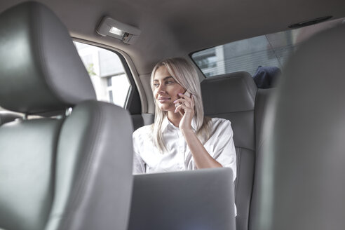 Smiling businesswoman on cell phone in car - VPIF00040