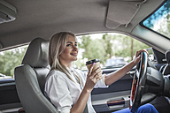 Smiling businesswoman holding takeaway coffee driving car - VPIF00049