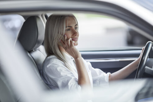 Businesswoman on cell phone driving car - VPIF00052