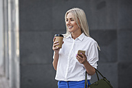Happy businesswoman with takeaway coffee and cell phone outdoors - VPIF00055
