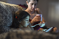 Mother feeding little girl in living room sofa while looking tablet - JASF01843