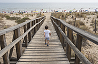 Spain, Huelva, back view of little boy running to the beach on boardwalk - JASF01844