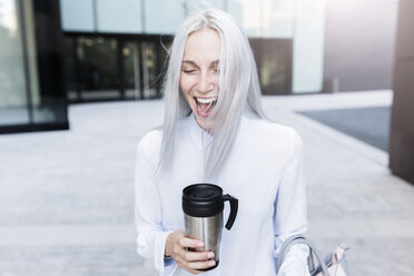 Screaming young businesswoman holding coffee mug in the city - GIOF03223