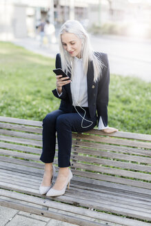 Young businesswoman sitting on bench with cell phone and earphones - GIOF03232