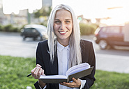 Portait of smiling young businesswoman with notebook in the city - GIOF03235