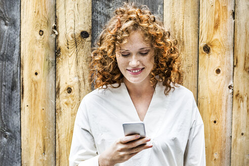 Portrait of smiling young woman looking at cell phone in front of wooden wall - FMKF04474