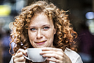 Portrait of smiling young woman with coffee cup - FMKF04480