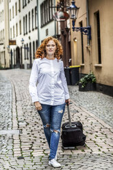 Germany, Cologne, young woman with suitcase in the old town - FMKF04486