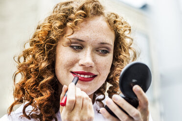 Portrait of freckled young woman applying lipstick - FMKF04489