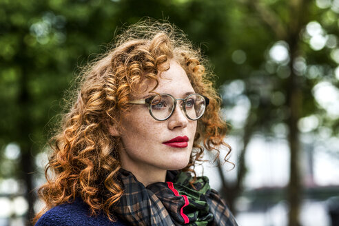 Portrait of redheaded young woman with red lips wearing glasses - FMKF04492