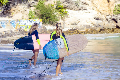 Indonesia, Bali, two women carrying surfboards at the sea - KNTF00884