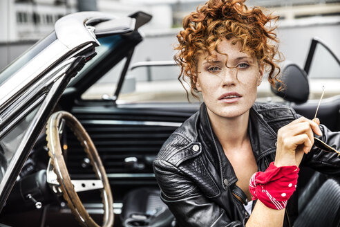 Portrait of confident redheaded woman in sports car - FMKF04497