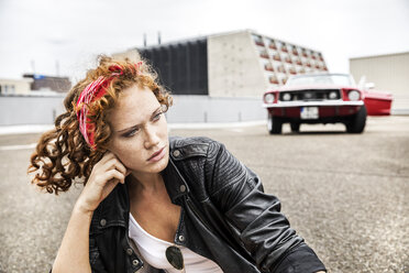 Portrait of confident redheaded woman sitting on parking level - FMKF04500