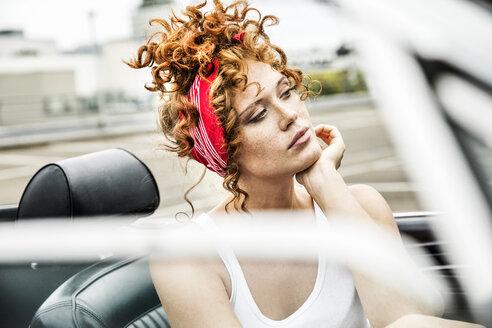 Portrait of redheaded woman in sports car - FMKF04503