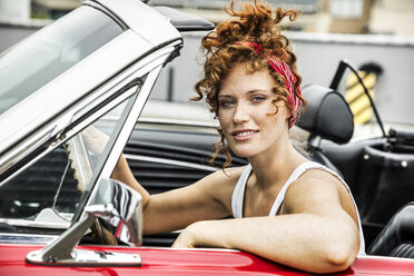 Portrait of smiling redheaded woman in sports car - FMKF04506