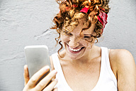 Happy redheaded woman holding cell phone - FMKF04509