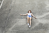 Young woman lying on parking level next to cell phone - FMKF04515