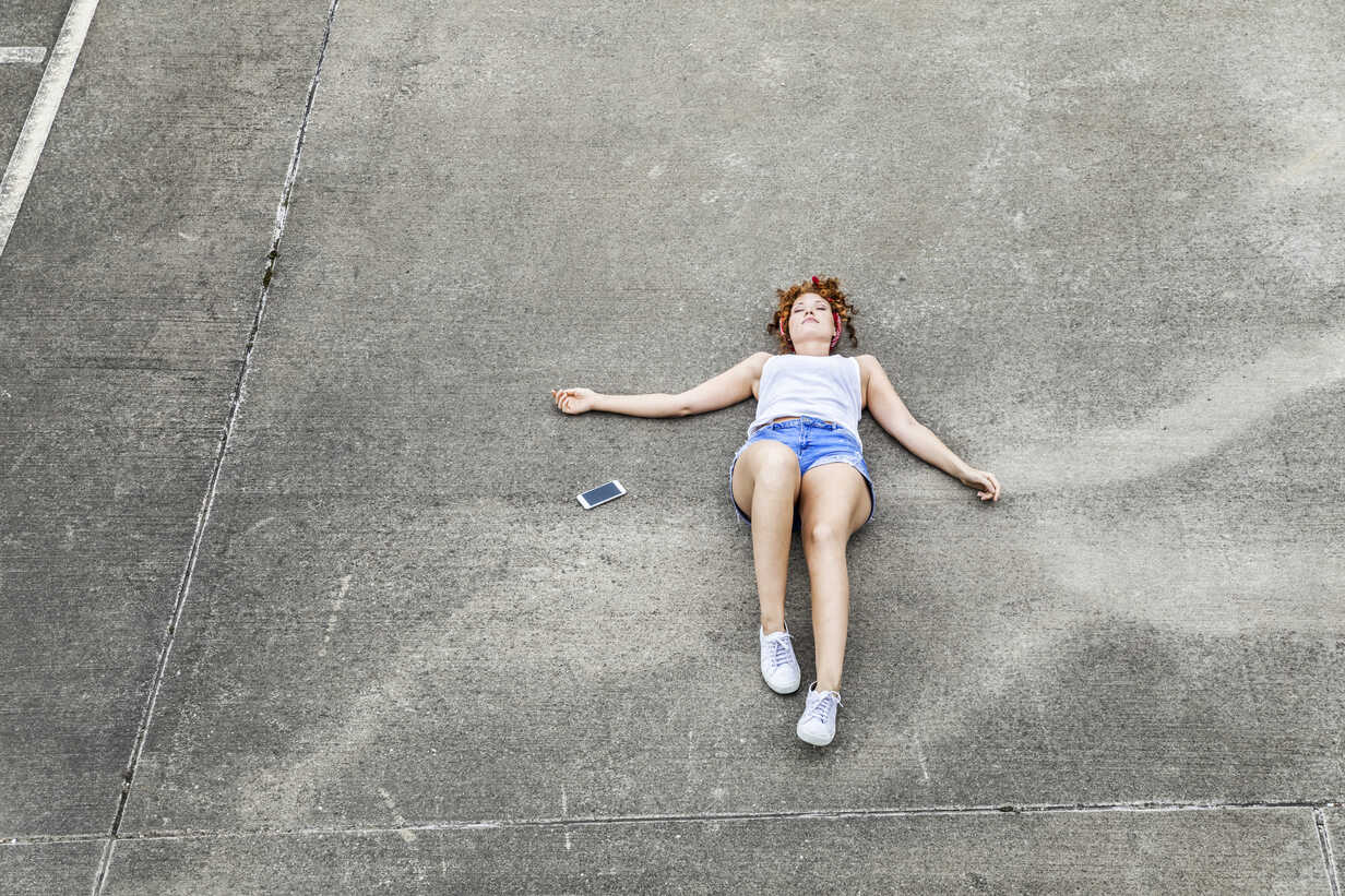Young woman lying on parking level next to cell phone - FMKF04515 - Jo Kirchherr/Westend61