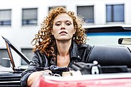 Portrait of confident redheaded woman in sports car - FMKF04518
