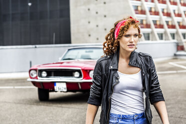 Redheaded woman next to sports car on parking level - FMKF04521