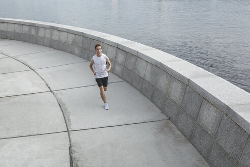 Young man running at the riverbank - VPIF00070