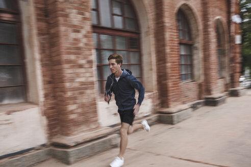 Young man running along brick building - VPIF00088