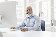 Smiling mature man with beard and glasses at desk - JOSF01701